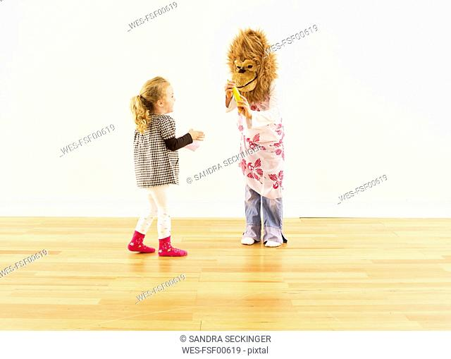 Two girls having fun with monkey mask