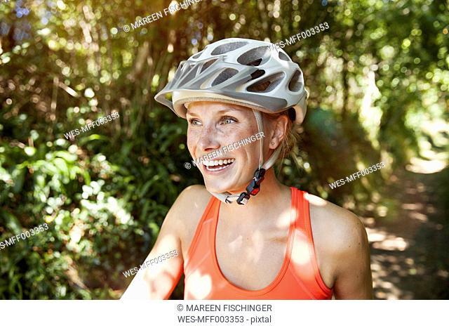 Laughing young woman with bicycle helmet