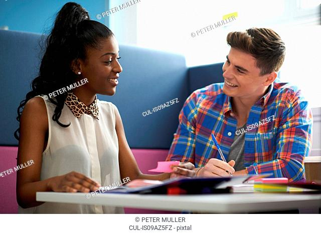 Young female and male college students discussing at desk