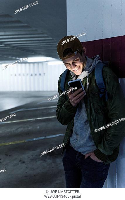 Smiling man looking at shining smartphone in parking garage