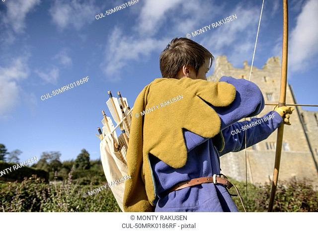 Student in period dress shooting arrow
