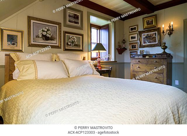 Queen size bed with antique wooden headboard, dresser and framed paintings in upstairs master bedroom inside an old circa 1805 Canadiana cottage style home