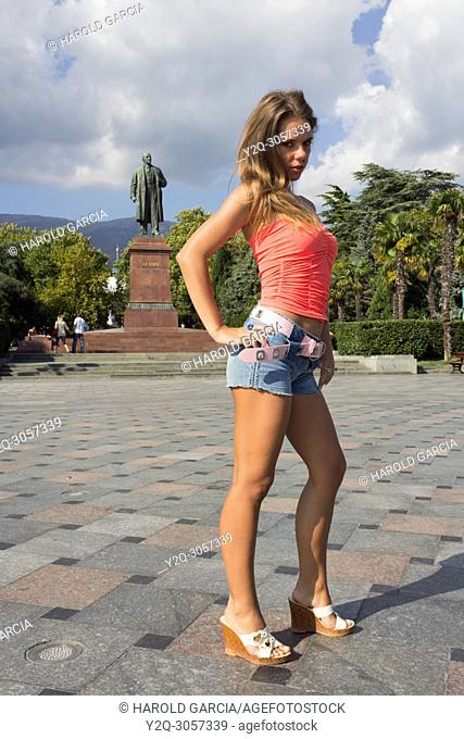 Beautiful woman posing in shorts and small shirt for the camera close to the Lenin's statue in park of Yalta, Crimea
