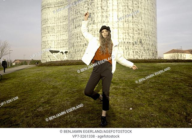 young student woman balancing on one leg in front of BTU university library IKMZ, in city Cottbus, Brandenburg, Germany