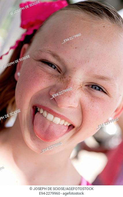 Portrait of a 10 year old girl with freckles sticking her tongue out at the camera making a funny face