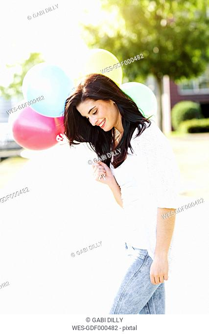 Smiling young woman with a bunch of balloons