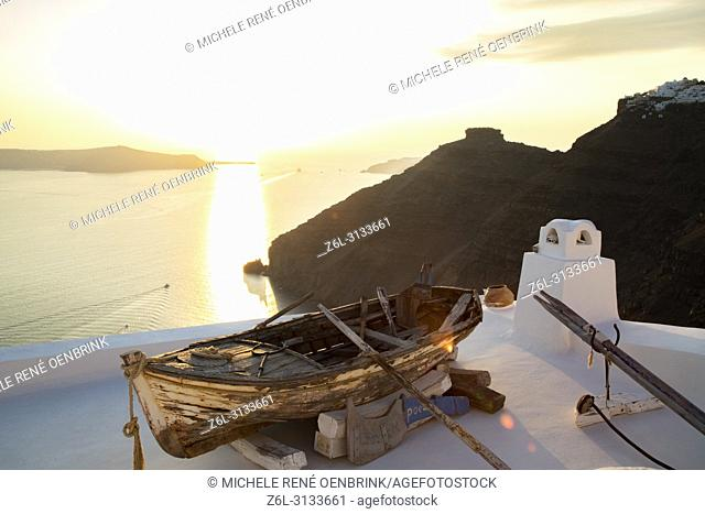 Scenic overlook of old row boat at sunset in Thira, Fira, Santorini Greece