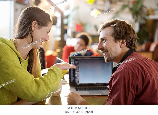 Couple using laptop at table