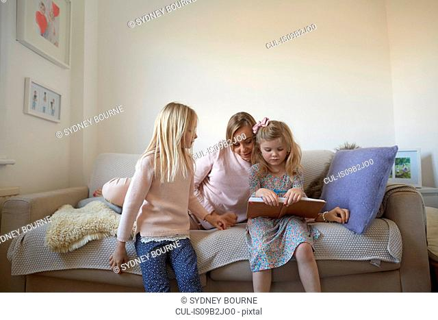 Mid adult woman and daughters reading storybook on sofa