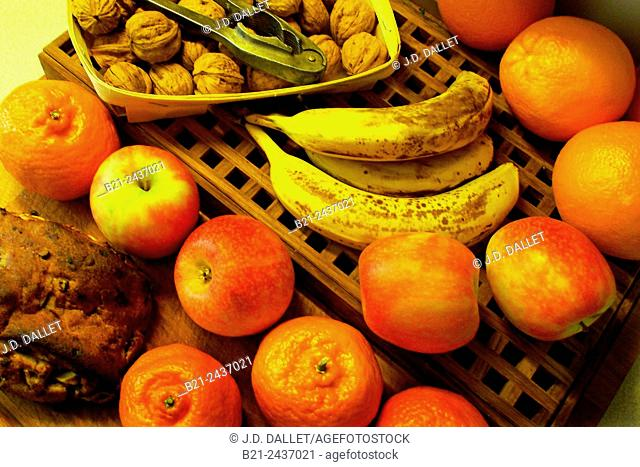 Bread and fruits, clementines, nuts, appples, oranges. .