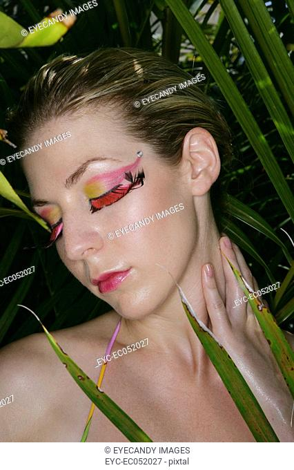 Woman in between green leaves with her eyes closed
