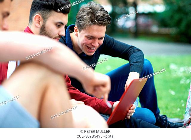 Three male friends, sitting outdoors, looking at digital tablet