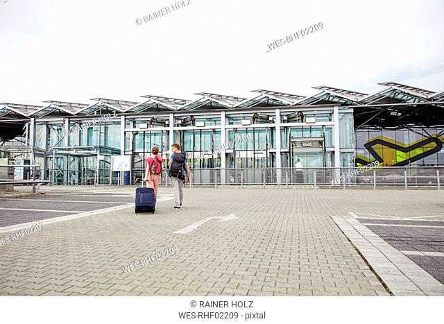 Rear view of couple walking outside airport