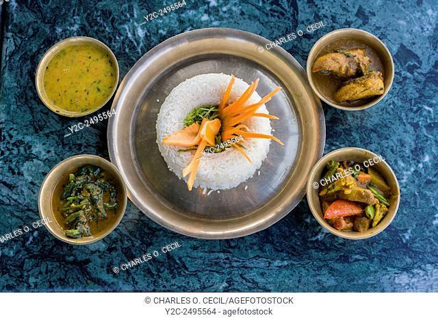 Nepal, Kathmandu, Swayambhunath. A Nepalese Lunch: rice, curried vegetables, chicken, spinach, lentil sauce