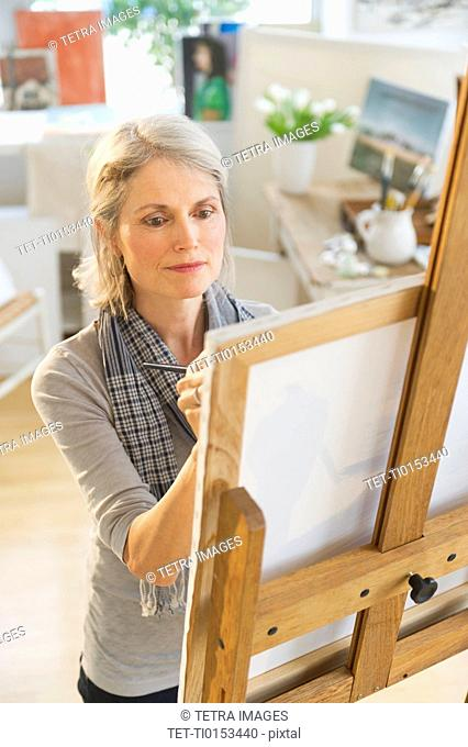 Portrait of senior woman painting on canvas
