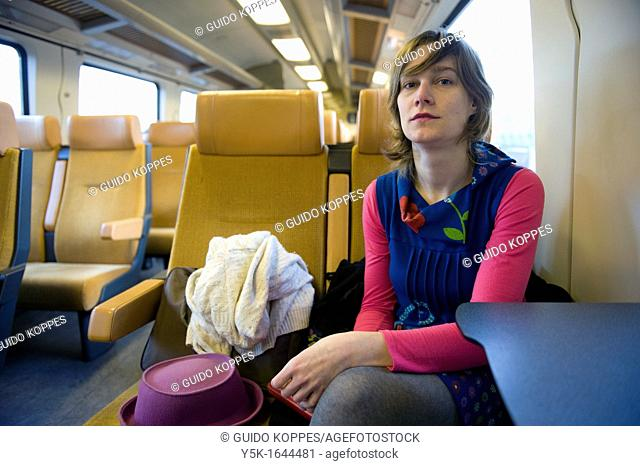 Rotterdam, Netherlands. A young, attractive woman, in colorfull wardrobe, traveling by intercity train from Rotterdam to Breda