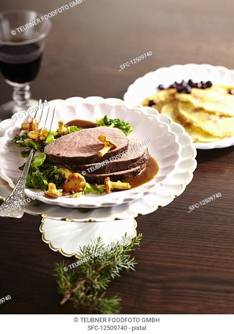 Roasted saddle of venison with savoy cabbage and chanterelle mushrooms and blueberry pancakes