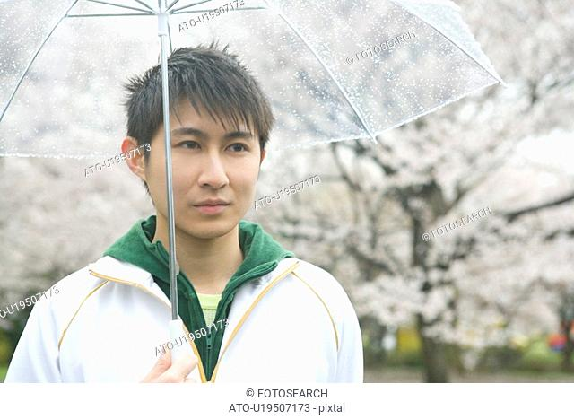 Portrait of a man holding an umbrella, front view, Japan