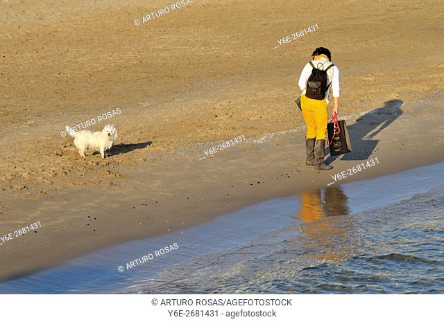 Woman and dog in Sitges beach (Barcelona), Catalonia