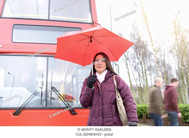 Passenger with umbrella in front of electric bus