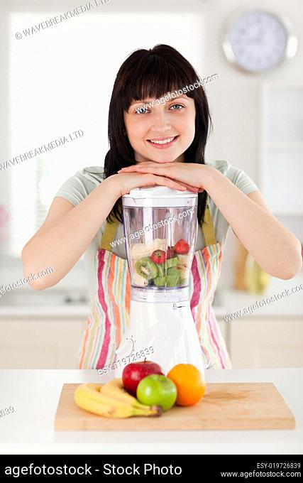Pretty brunette woman posing with a mixer while standing