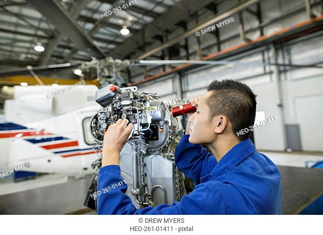 Focused mechanic examining helicopter part in airplane hangar