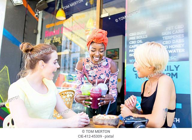 Young women friends enjoying smoothies at sidewalk cafe