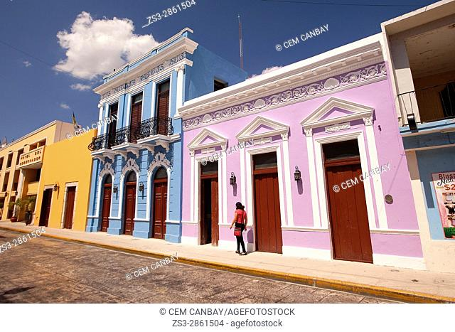 Woman walking in front of the colorful colonial buildings in the city center, Merida, Yucatan Province, Mexico, Central America