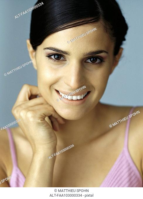 Woman smiling at camera, hand under chin, portrait