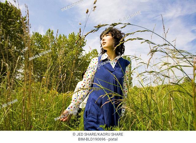 Asian woman walking through tall grass