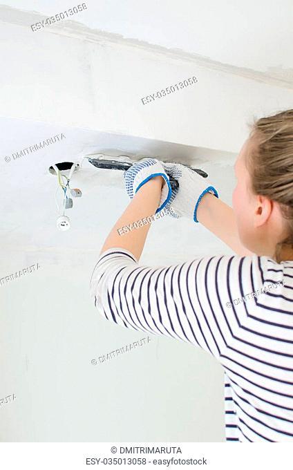 Female worker repairs gypsum plasterboard frame with spackling paste