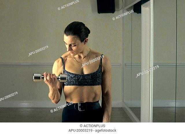 Woman checking posture whilst working with hand weights
