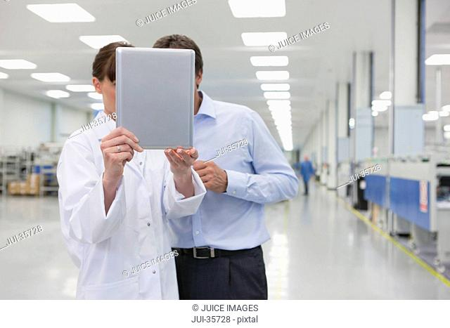 Scientist and businessman looking at digital tablet in hi-tech manufacturing plant