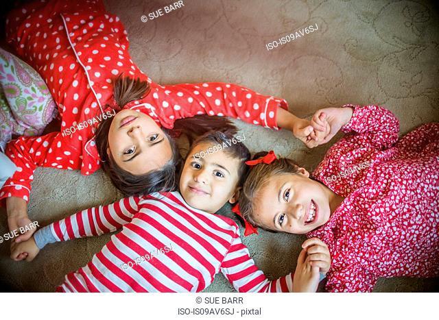 Overhead view of children wearing pyjamas lying on carpet looking at camera smiling