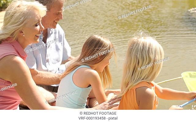Grandparents and two granddaughters fishing with net in pond in park