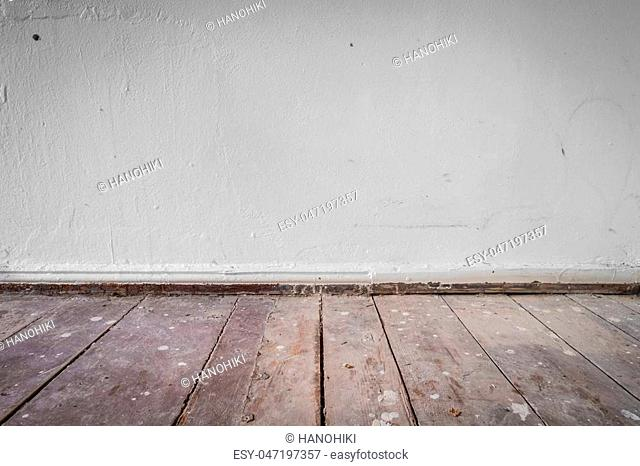wooden floor and dirty wall - apartment construction concept background -