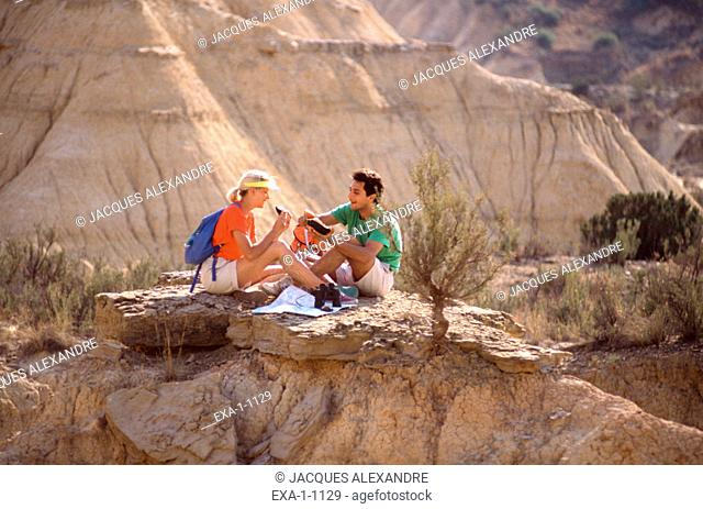 Couple with backpacks on rock cliffs