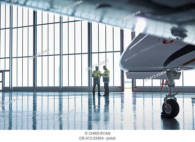 Air traffic control ground crew workers talking in airplane hangar