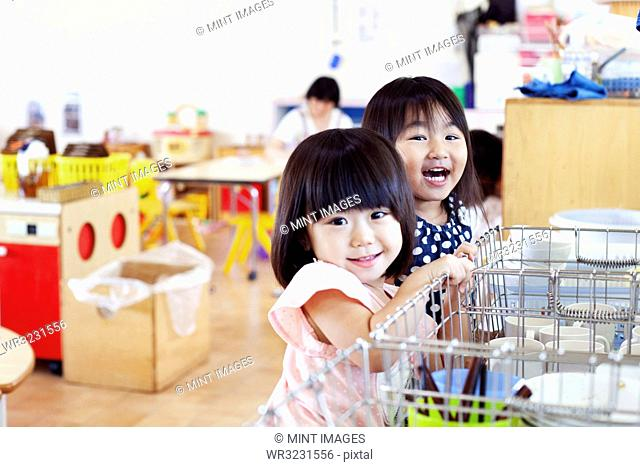 Two smiling girls in a Japanese preschool, looking at camera