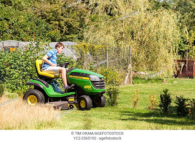 A 15 year old boy mowing the lawn on a John Deere ride on mower in the Uk