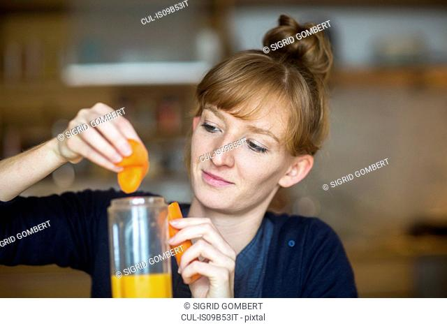Young woman making smoothie with fresh carrot