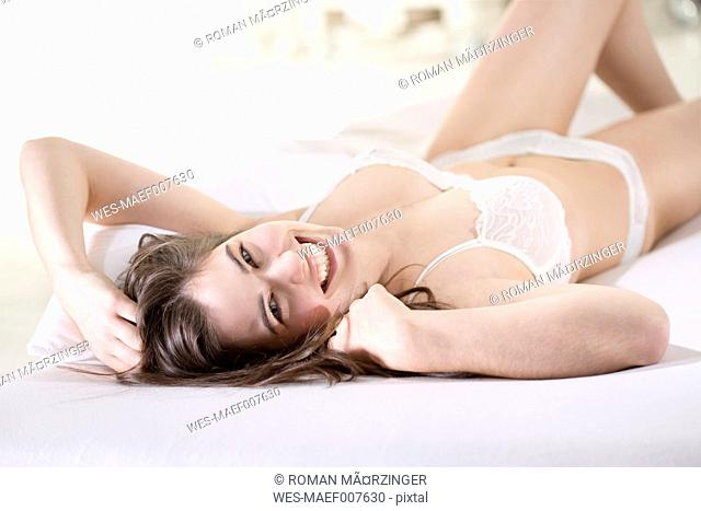 Smiling young woman wearing white bra and panties lying on back on bed