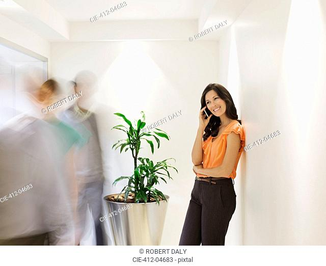 Businesswoman talking on cell phone in busy office hallway