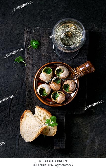 Escargots de Bourgogne - Snails with herbs butter, in traditional ceramic pan with parsley, bread and glass of white wine on wooden chopping board over black...