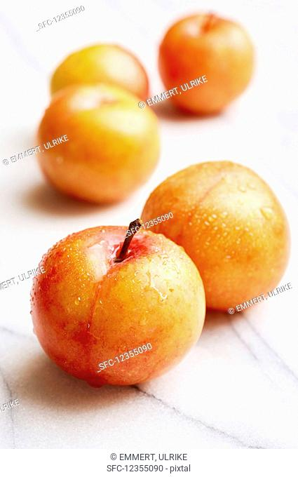 Yellow plums on a white marble plate