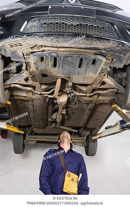 Auto mechanic working under a raised car in a garage