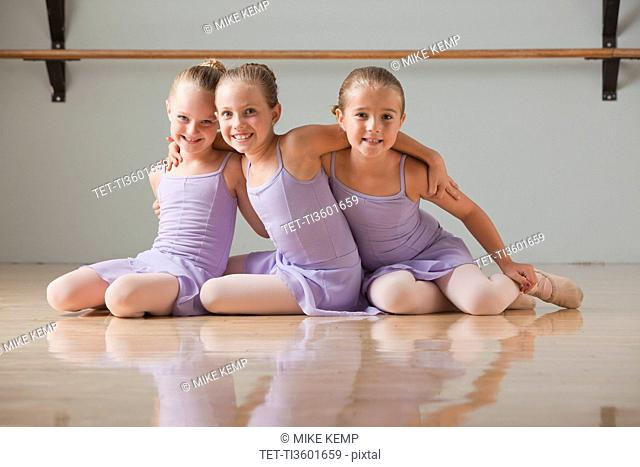 Portrait of female ballet dancers 6-7 embracing in dance studio