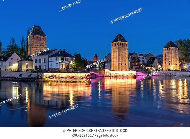 towers of the medieval bridge Ponts Couverts and Ill river in Strasbourg at night, Alsace, France