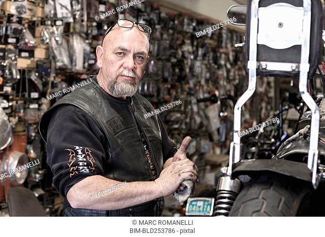 Caucasian man repairing motorcycle and wiping hands