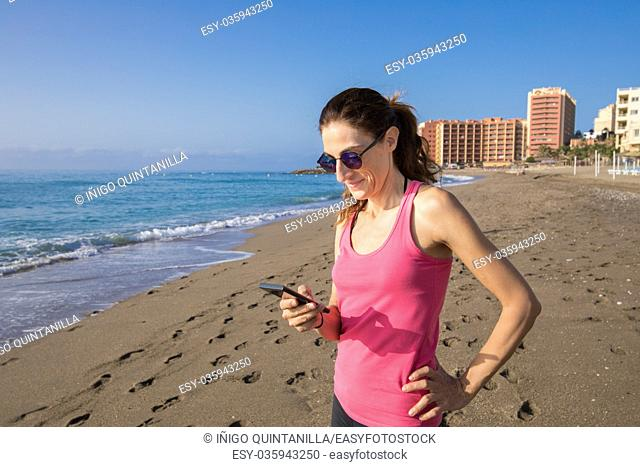 woman with pink sleeveless t-shirt smiling and touching mobile phone smartphone at beach with sea and buildings behind in Benalmadena, Malaga, Andalusia, Spain